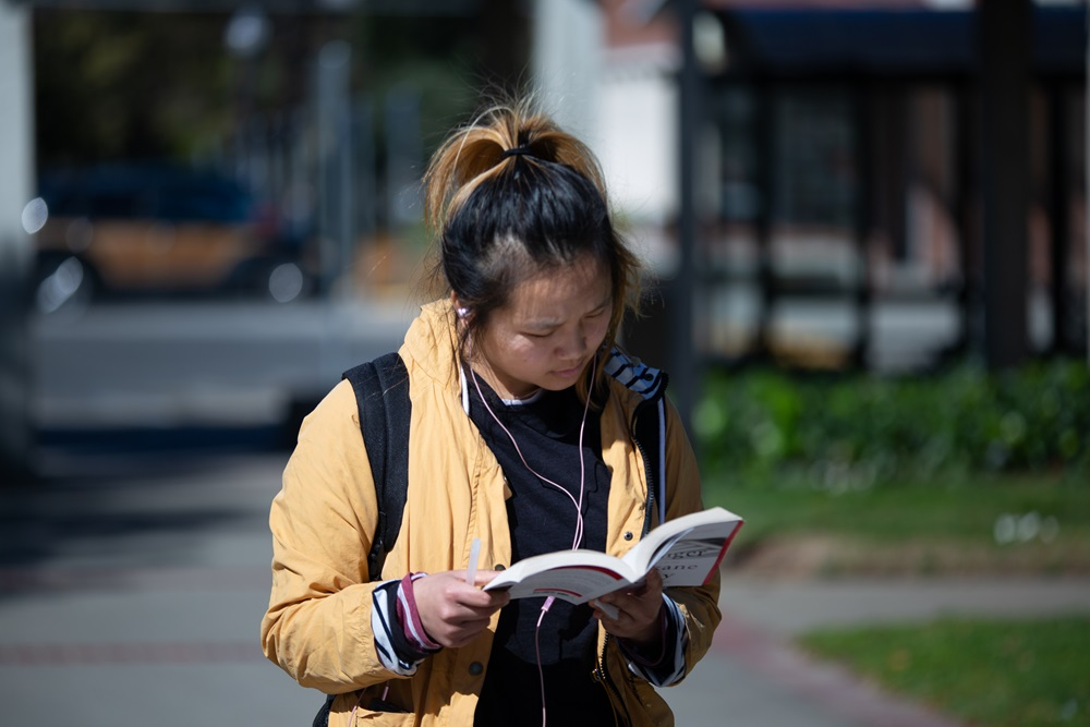 Student reads a book while walking at Sacramento City Campus.