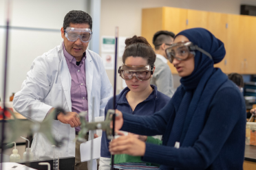 Teacher and students wearing protective eye wear and working in a science lab